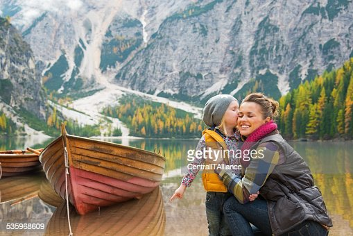 Portrait of baby kissing mother on lake braies, italy : Stock Photo