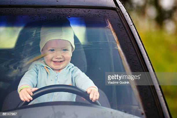 portrait of baby sitting behind steering wheel of car