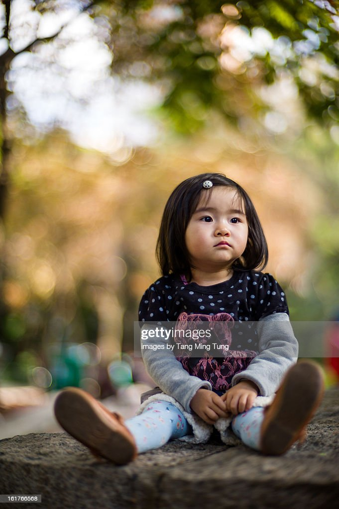Portrait of baby sitting in a park looking away : Stock Photo