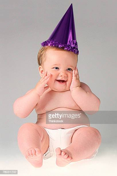 Portrait of baby wearing purple party hat and smiling with hands at her cheeks