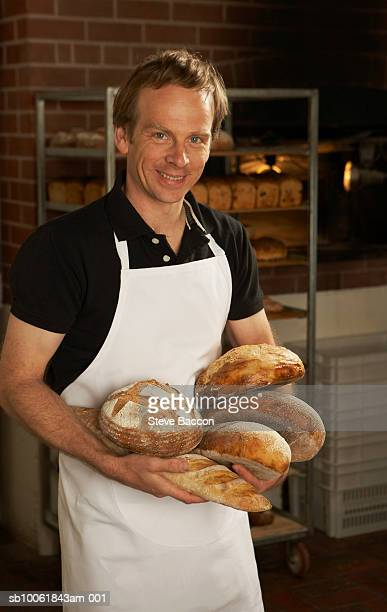 Portrait of baker in apron carrying loaves of freshly baked bread
