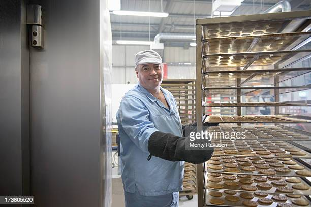 Portrait of baker with trays of freshly baked biscuits in food factory