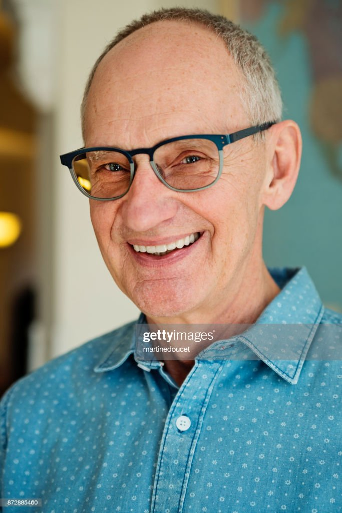 Portrait of bald senior man with glasses smiling. : Stock Photo