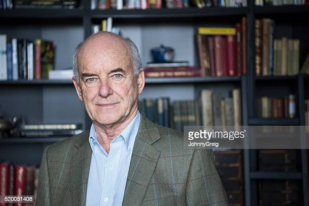 Portrait of balding senior man in front of bookcases