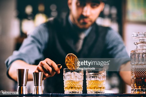 Portrait of barman adding ingredients and creating cocktail drinks on bar counter : Stock Photo