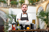 Portrait of handsome barman in uniform with bottles and shaker at the restaurant