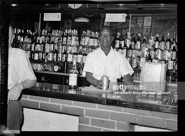 Portrait of bartender Louis 'Blue' Geary holding mint julep beside bottle of Cobbs Creek at bar in Crawford Grill No 1 Pittsburgh Pennsylvania August...