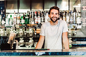 Portrait of smiling bartender. Man is wearing casuals. He is standing at bar counter.