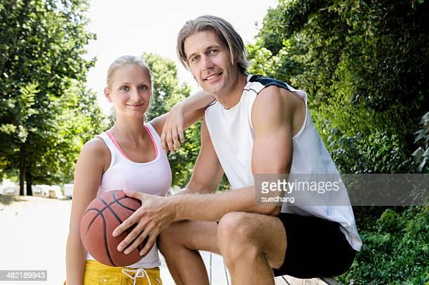 Portrait of basketball couple taking a break in park