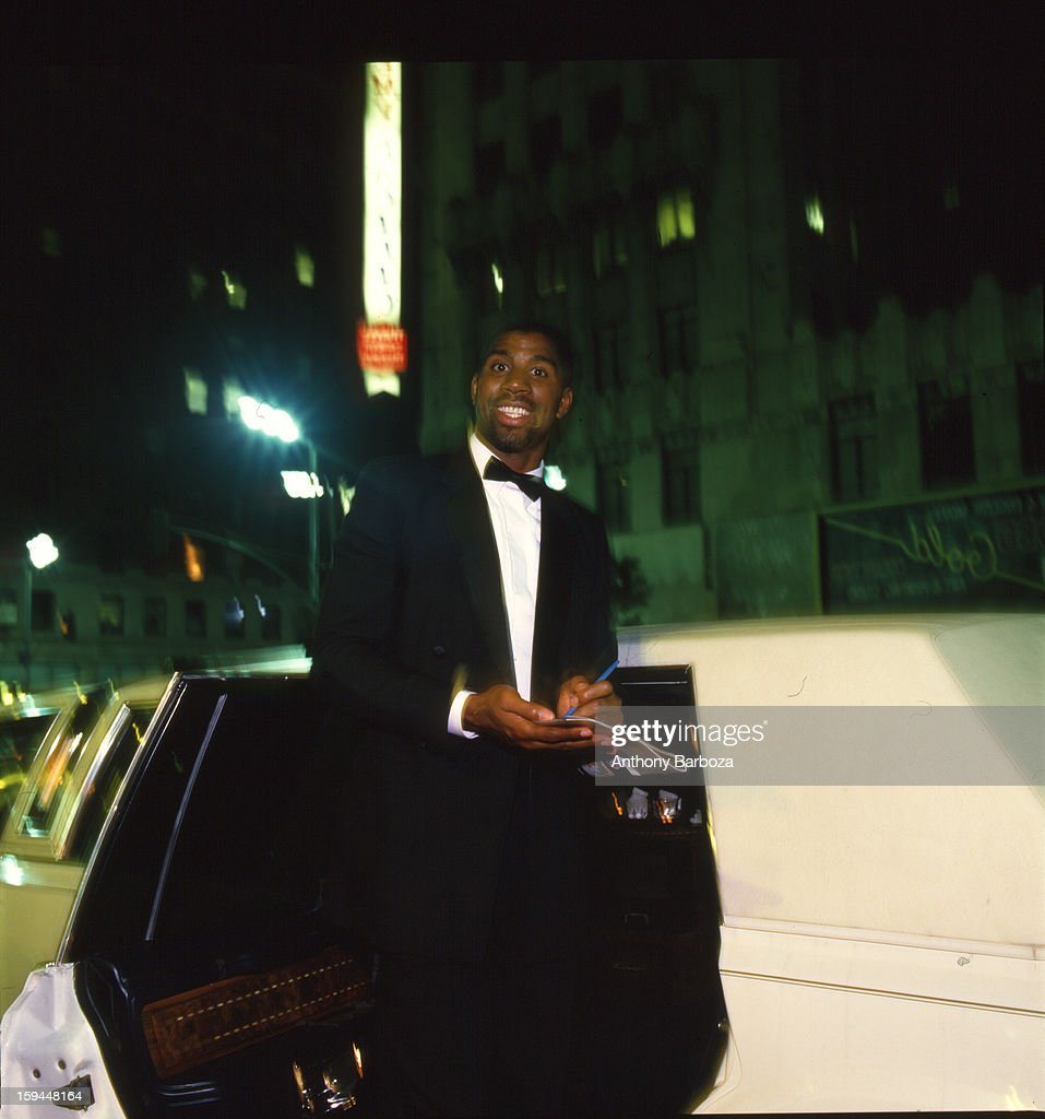 Portrait of basketball player Magic Johnson in black tie as he signs an autograph beside the open door of a white stretch limousine 1980s