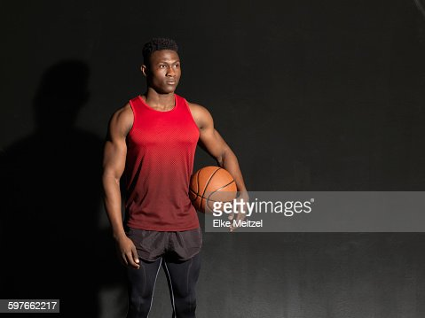 Portrait of basketball player with ball, black background