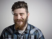 Portrait of bearded man smiling with eyes closed.