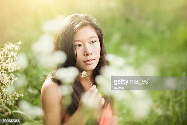 Portrait of Beautiful Asian girl in meadow holding wild flowers.