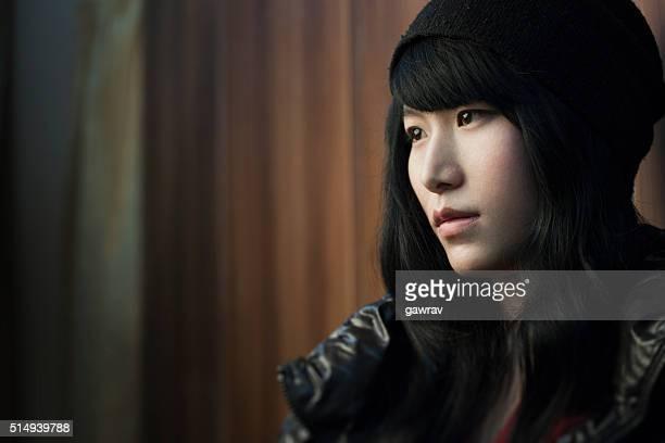 Portrait of beautiful Asian serene late teen girl looking away.