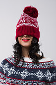 Portrait of beautiful brunette girl with knitted beanie on her face. Christmas mood