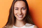Portrait of beautiful brunette in orange studio
