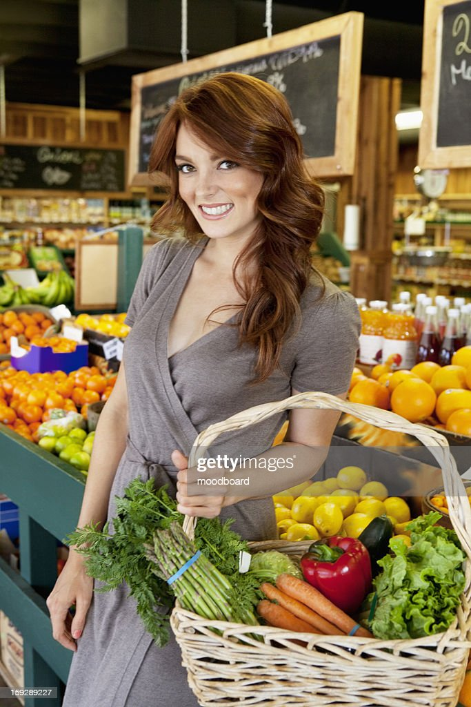 Portrait of beautiful brunette with basket shopping in market : Stock Photo