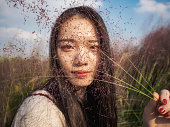 Portrait of beautiful Chinese girl holding Pink hairawn muhly, focused on the pink seeds.