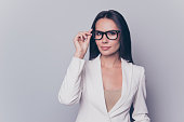 Portrait of beautiful clever gorgeous stunning charming woman with black hair wearing white  jacket, she is trying on new glasses, isolated on grey background, copyspace
