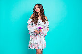 Portrait of beautiful curly brunette hold small purple bouquet of flowers in hands and aside stand isolated on shine turquoise background