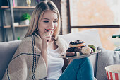 Portrait of beautiful emotional charming attractive sweet toothy woman sitting on sofa in living room, holding plate of donuts and macaroons, looking exciting satisfied