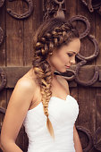 Portrait of a beautiful young woman dressed in wedding dress. She has a natural blonde and hairstyle with a braid. Behind her is a wooden door with horseshoes on it.