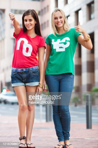 Portrait of beautiful female friends smiling and gesturing : Stock Photo