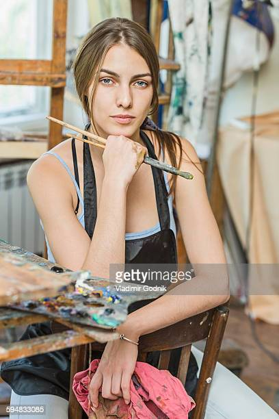 Portrait of beautiful female painter sitting on chair in studio