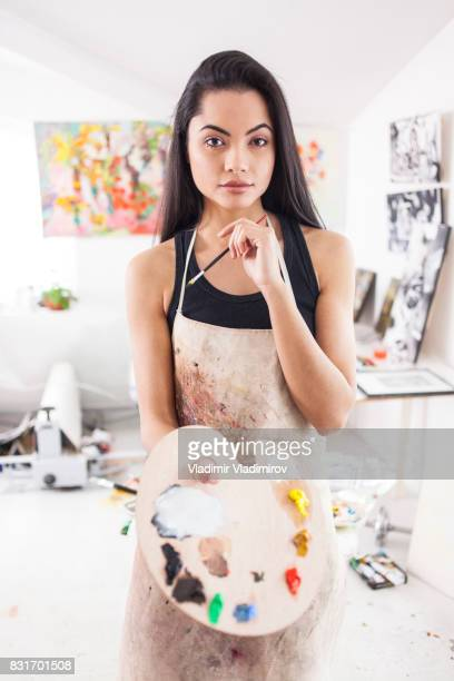 Portrait of beautiful fine artist with palette and paintbrush