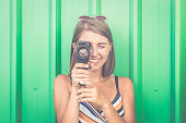 Portrait of a young smiling woman filming with retro camera isolated on green background.