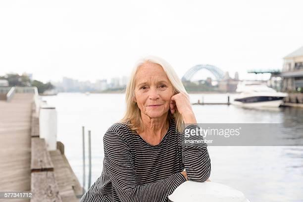 Portrait of beautiful happy blond mature woman standing  near water