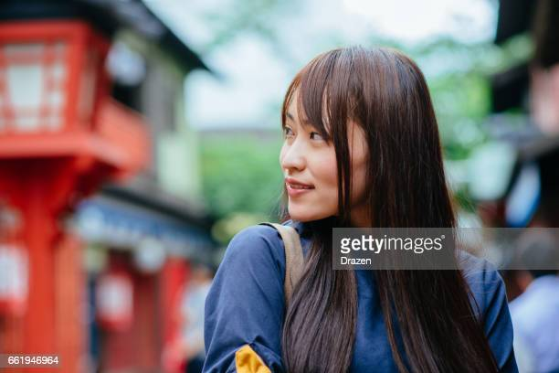 Portrait of beautiful Japanese young woman enjoying day off outdoors in historical Japanese village