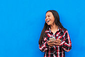 Portrait of beautiful latino girl using the mobile in the street. Childhood Concept.
