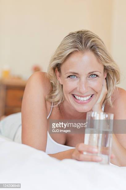 Portrait of beautiful mature woman lying in bed with a glass of water