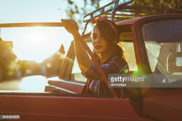 Portrait of beautiful pin-up woman holding a door of a vintage car