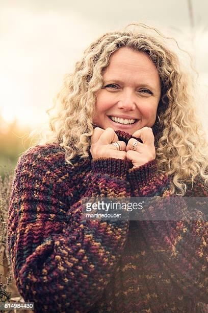 Portrait of beautiful real woman in corn field autumn sunset.