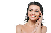 Beauty portrait of young brunette woman face with wet hair and natural clean look isolated on white background