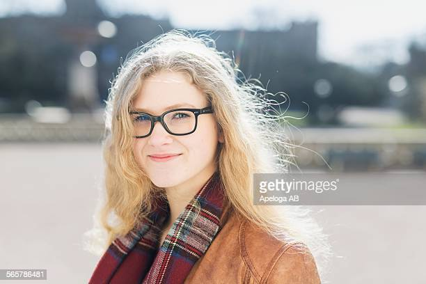 Portrait of beautiful teenage girl wearing glasses outdoors