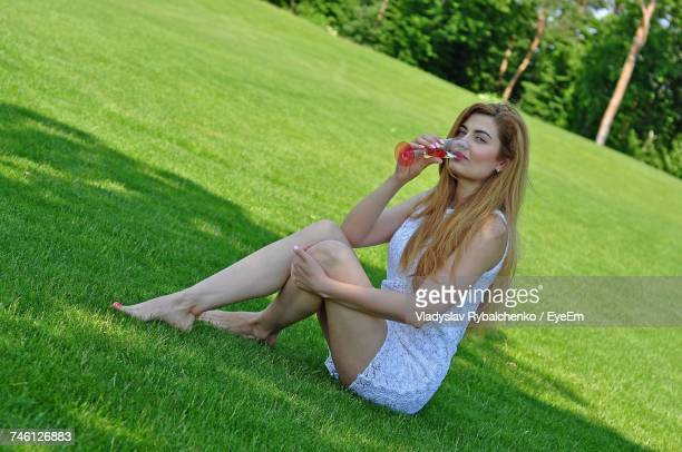 Portrait Of Beautiful Woman Having Drink While Sitting On Grassy Field At Park
