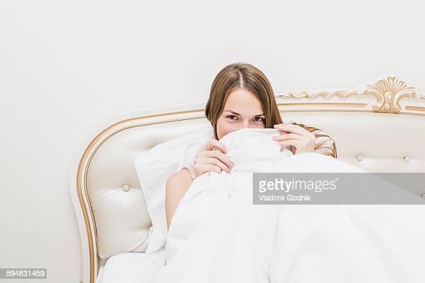 Portrait of beautiful woman hiding in duvet at home