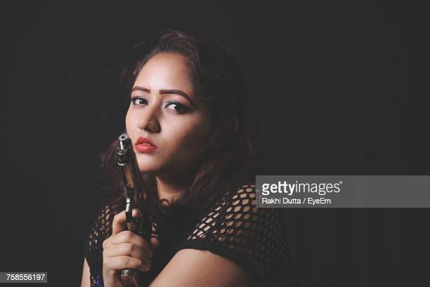 Portrait Of Beautiful Woman Holding Handgun In Darkroom