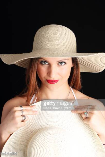 Portrait Of Beautiful Woman Holding Hat Against Black Background