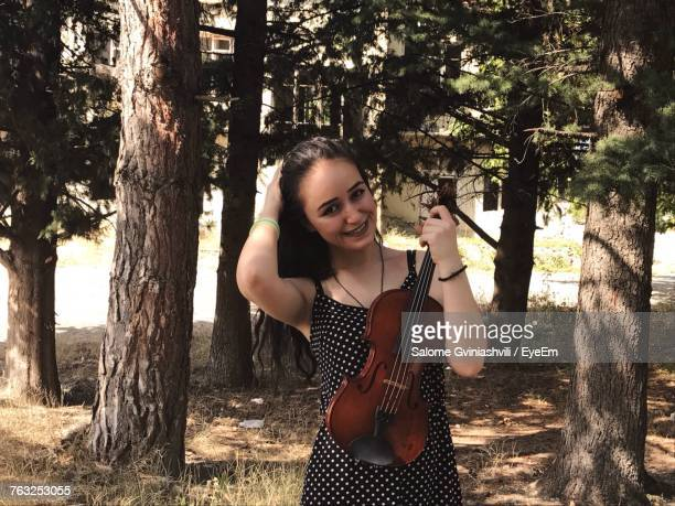 Portrait Of Beautiful Woman Holding Violin Against Trees