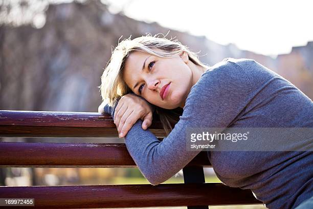 Portrait of beautiful woman leaned on the bench.