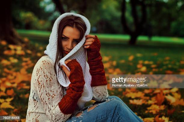 Portrait Of Beautiful Woman Sitting At Park During Autumn