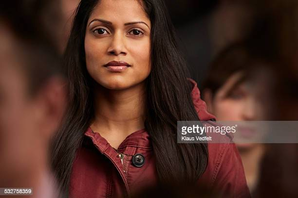 Portrait of beautiful woman, standing in crowd