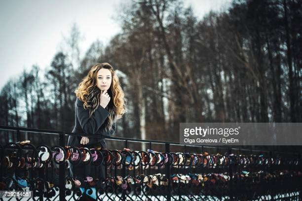 Portrait Of Beautiful Woman With Hand On Chin Leaning On Railing With Love Locks