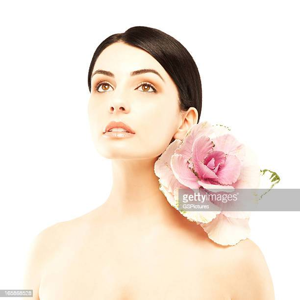 Portrait of beautiful woman with pink flower on her shoulder