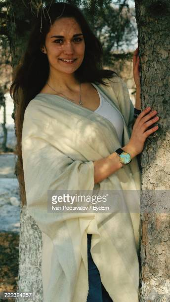 Portrait Of Beautiful Woman With White Shawl Standing By Tree Trunk At Park