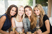 Portrait of beautiful women smiling and having drinks at the party